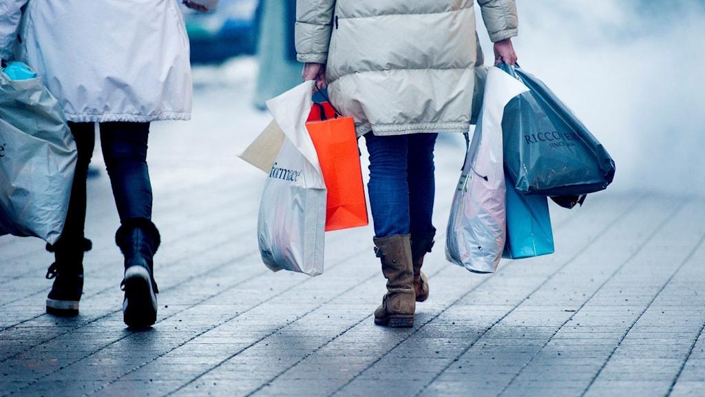 Kvinna bär flera shoppingkassar.