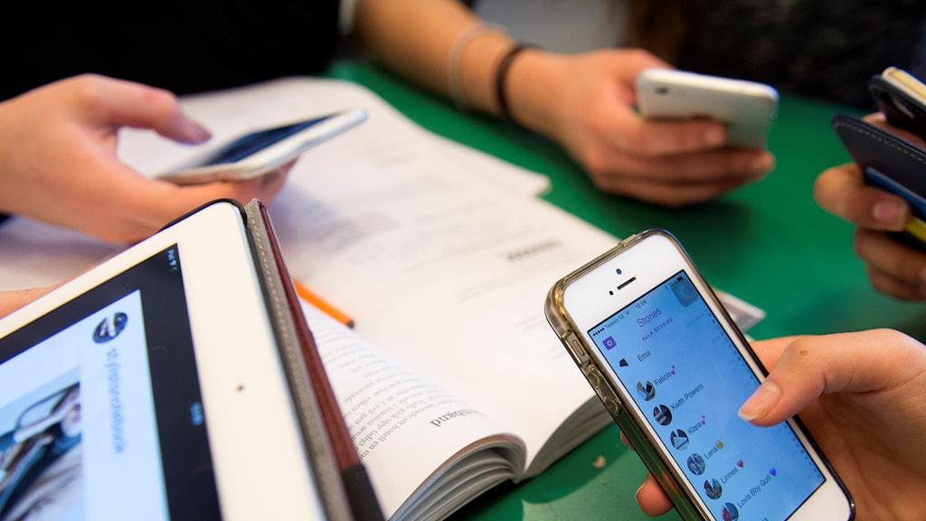 flera personer använder sina smartphones