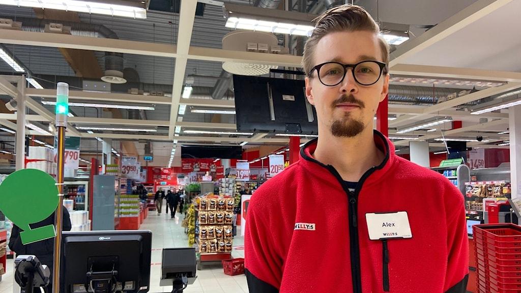 Närbild på en ung man med skägg och glasögon som står i en mataffär, han är iklädd affärens röda tröja.