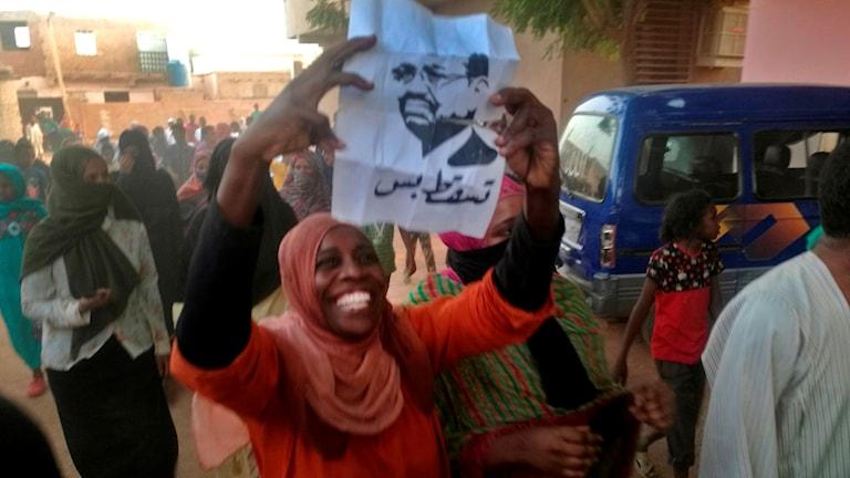 En demonstrant håller upp en bild på president Omar al-Bashir.