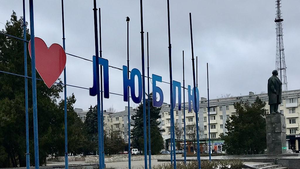 """""""Jag älskar Luhansk"""", står det på torget vid Lenin-statyn. Foto: Jesper Lindau/Sveriges Radio."""