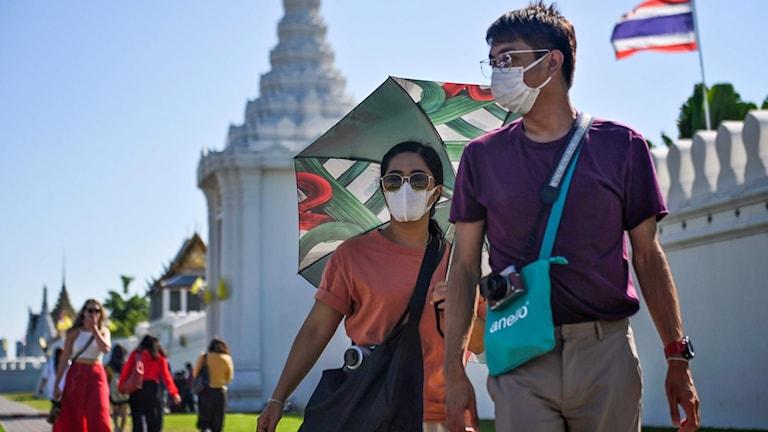 Människor vandrar runt med ansiktsmask utanför Stora Palatsen i Bangkok, 27 januari 2020. Foto: Lillian Suwanrumpha/TT.