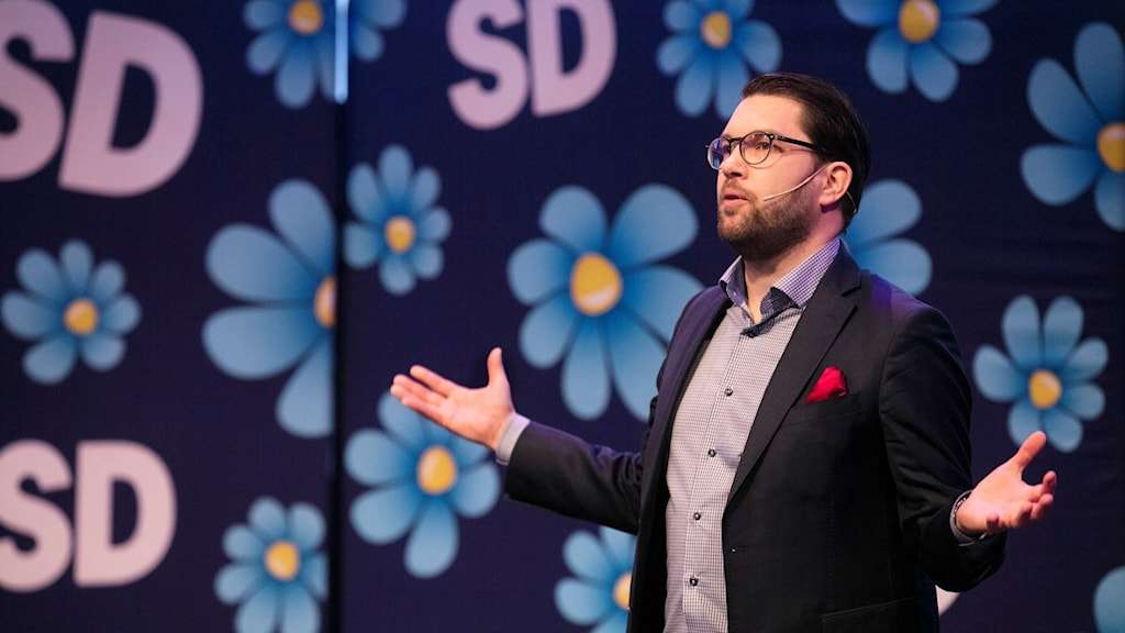 Man in glasses and suit, talking on a stage, infront of the Sweden Democrat logo.