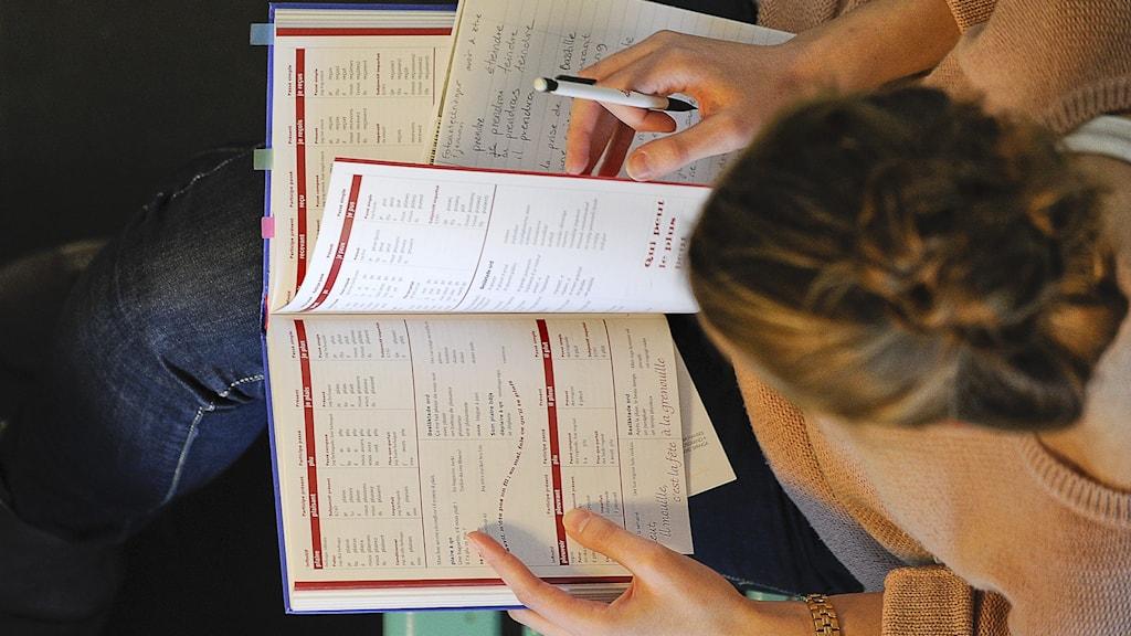 Kvinnlig student med böcker sedd ovanifrån.
