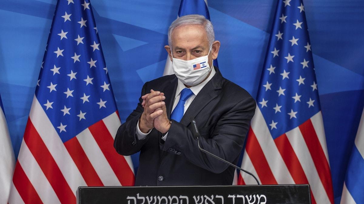 Israels premiärminister Benjamin Netanyahu framför amerikanska flaggor.