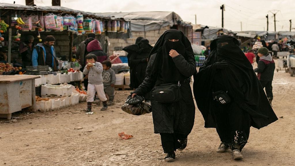 Två kvinnor går i svart burka.