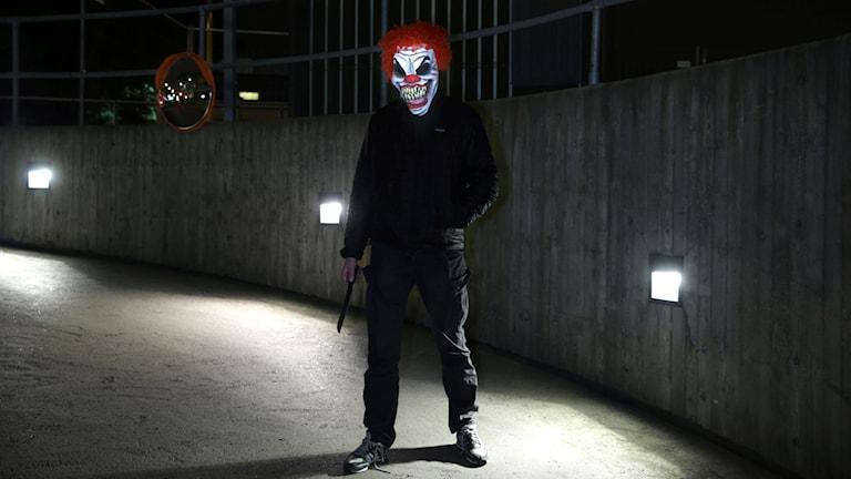 Bild på man med clownmask beväpnad med kniv.