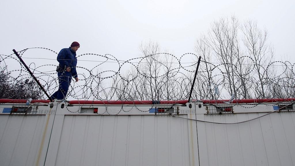 En vakt går på en container med taggtråd på.