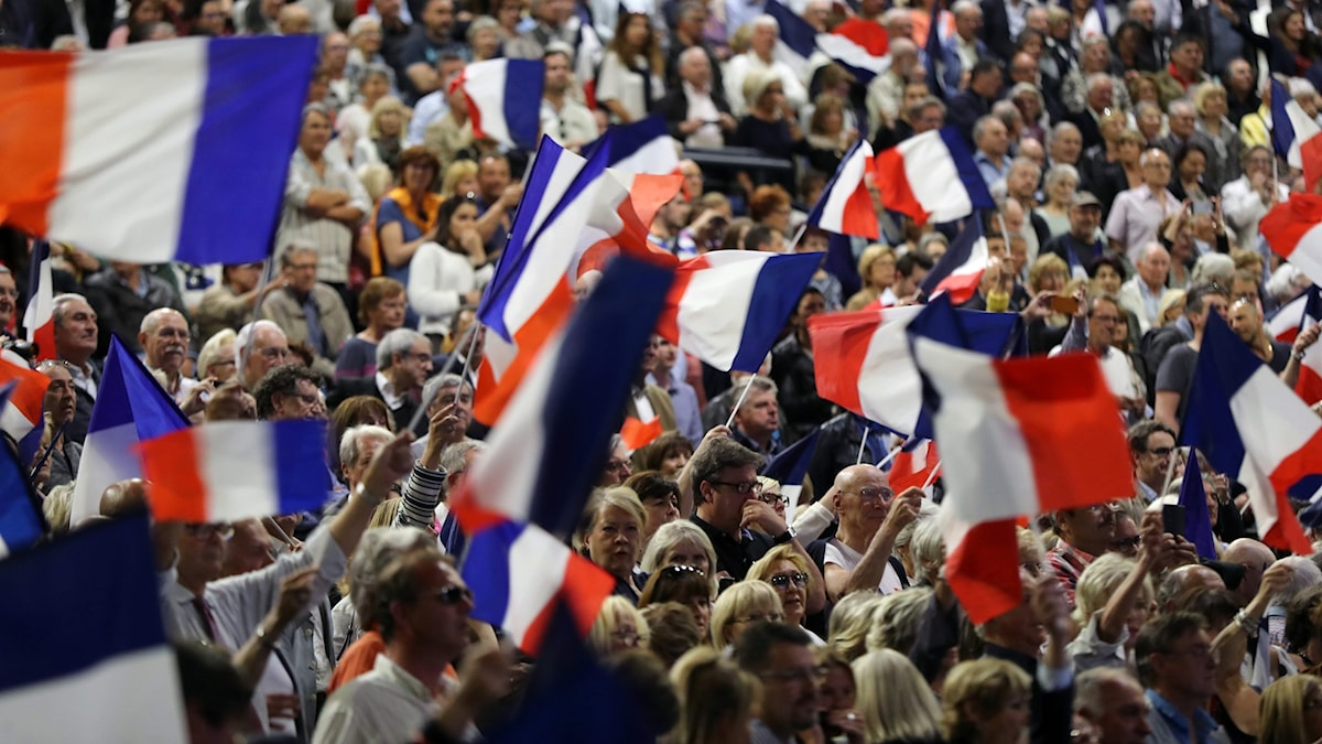 Franska flaggor i ett folkhav.