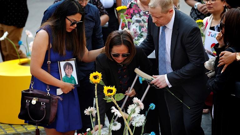 Två kvinnor och en man lägger blommor vid en minnesplats.