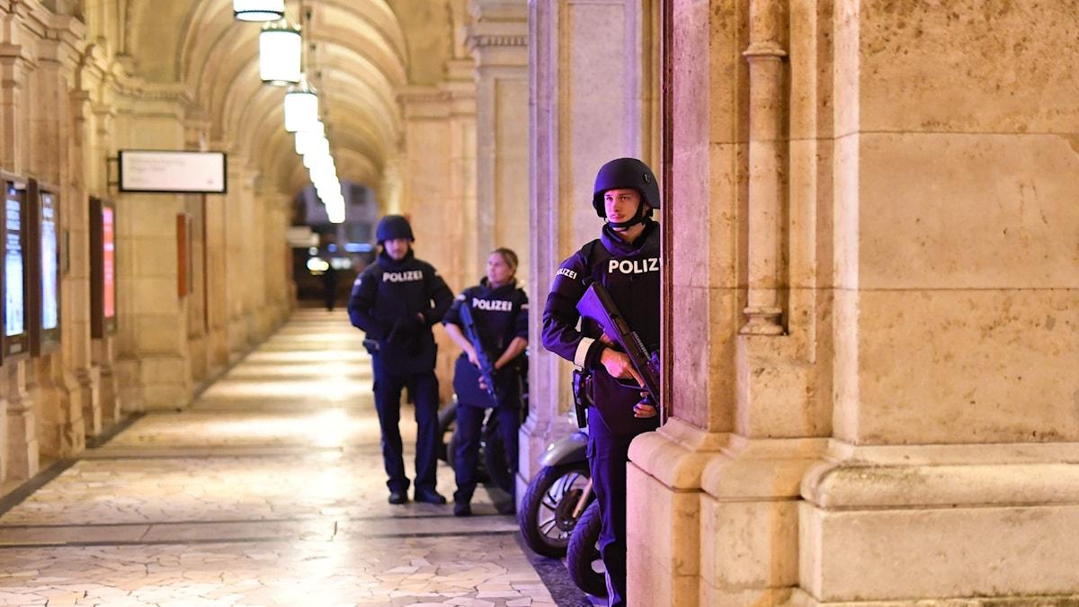 Tre poliser står upp och två hat vapen i händerna.