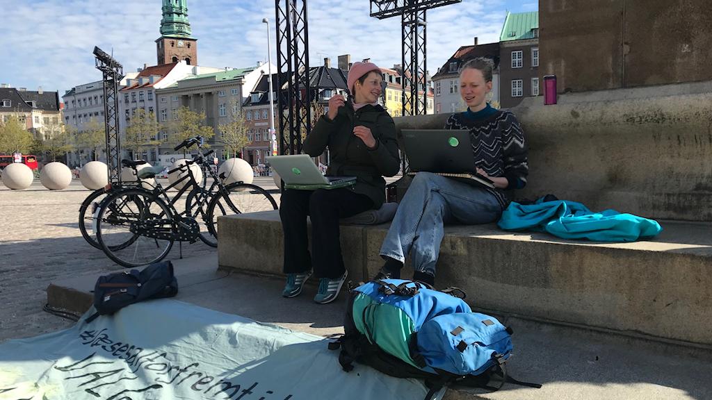 Studenten Helene Barlebo (t.v.) sitter med en vän och demonstrerar för klimatet utanför det danska parlamentet, Folketinget.