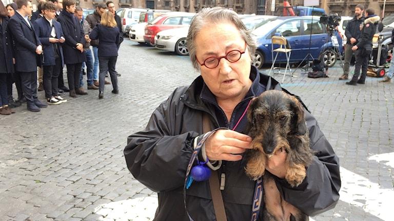 Luigina Lotti står utanför en vallokal med en hund i famnen. I bakgrunden väntar ungdomar på Silvio Berlusconi.