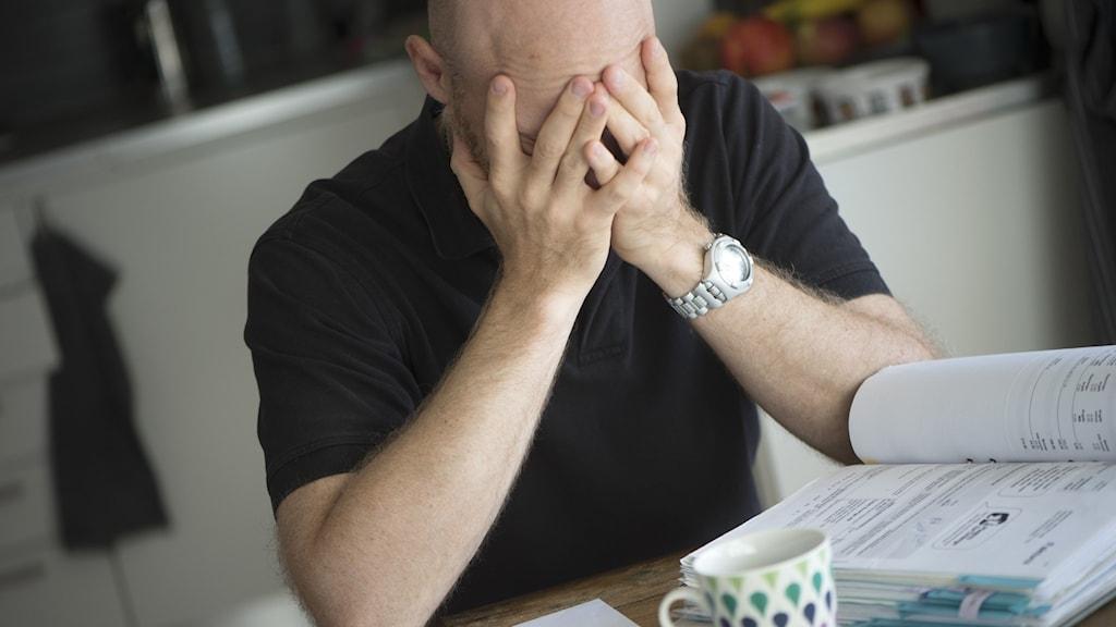 En man som sitter vid ett bord med ansiktet gömt i händerna.