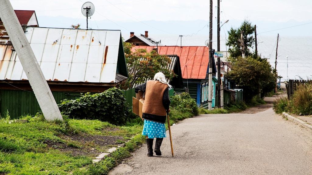 En gammal kvinna på en tom gata i Sibirien.