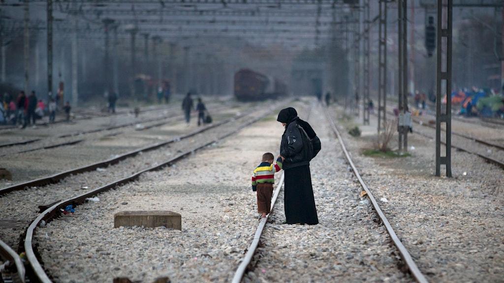 Kvinna håller barn som balanserar på järnvägsspår i handen.