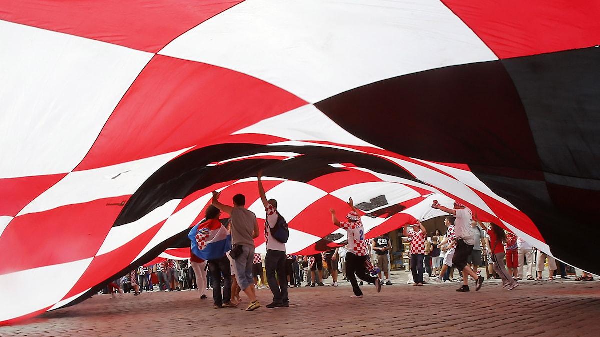 Kroater under en stor kroatisk flagga.