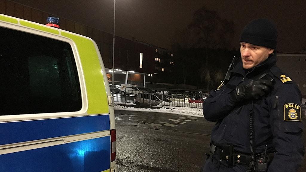 Polis i Göteborg står vid polisbil och pratar i telefon.