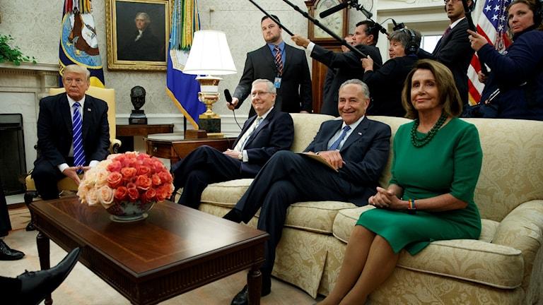 Fyra personer sitter runt ett bord, bakom står folk med kameror och mikrofoner.