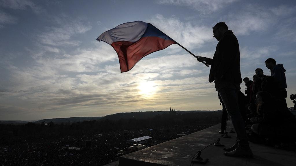 en person som har en tjeckisk flagga i handen.