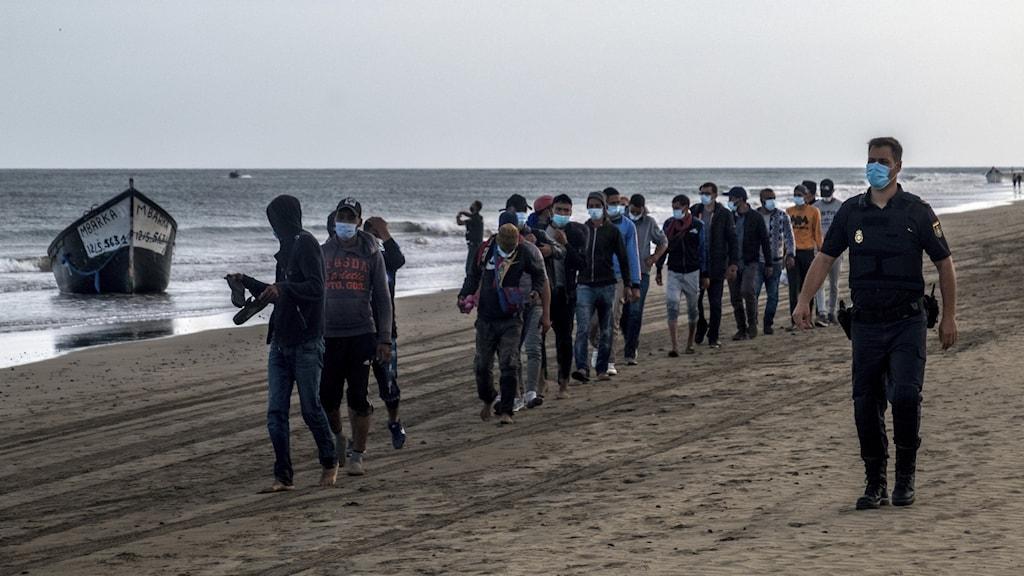 Migranter går på en strand övervakade av en polis med munskydd.