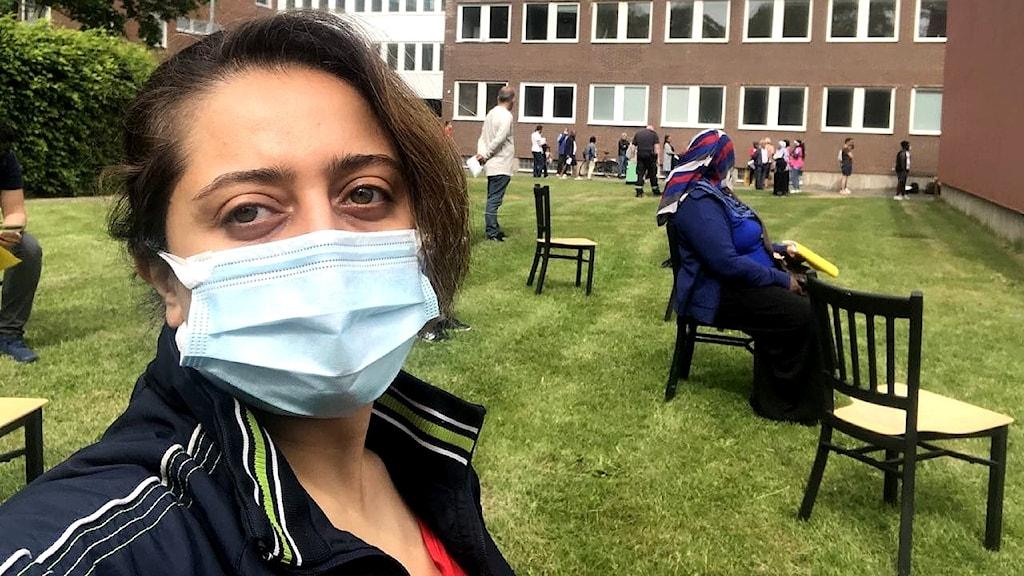 Aso (kvinna) står med munskydd utomhus, framför asylboendet Restad Gård. I bakgrunden står stolar utställda på en gräsmatta. På några av stolarna sitter det personer.