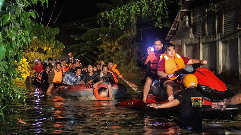 Människor evakueras i gummibåtar på grund av översvämningar.
