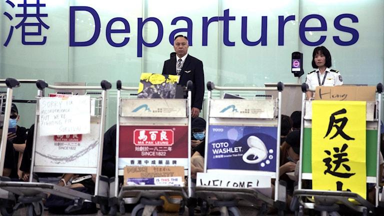 Flygplatspersonal vid Hongkongs flygplats under tisdagskvällen.