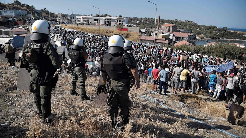 Kravallpoliser står framför en folkmassa vid vägspärren till Mytilini.