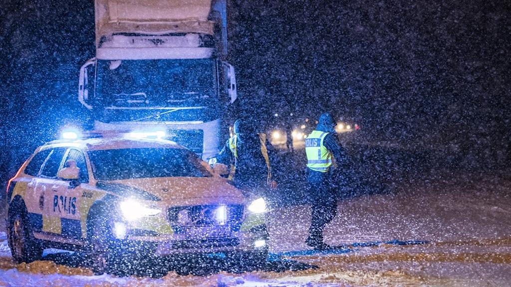 En polisbil står vid en stillastående lastbil på en väg i kraftigt snöoväder.