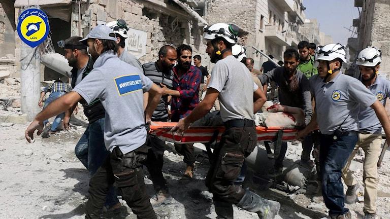 Medlemmar i Vita Hjälmarna inspekterar skador efter ett bombanfall i Aleppo.