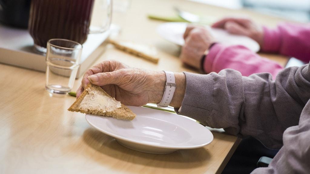 Man sitter med en smörgås i handen med lite smör på.