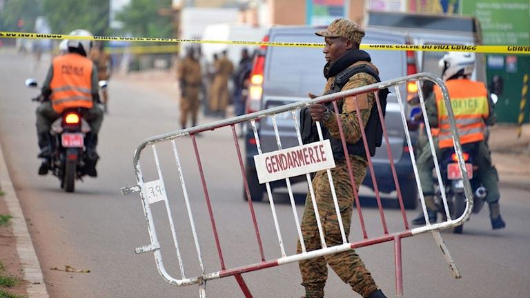 En polis går med ett kravallstaket på en gata.