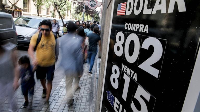 Människor på gata går förbi skylt med valutaväxlingskurs.
