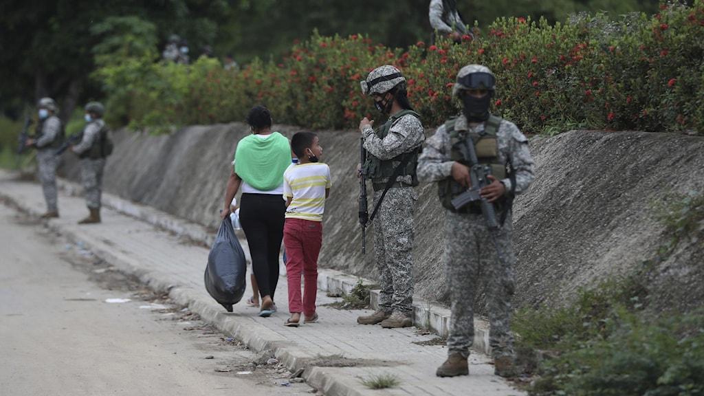 Militär på gatan med två barn.