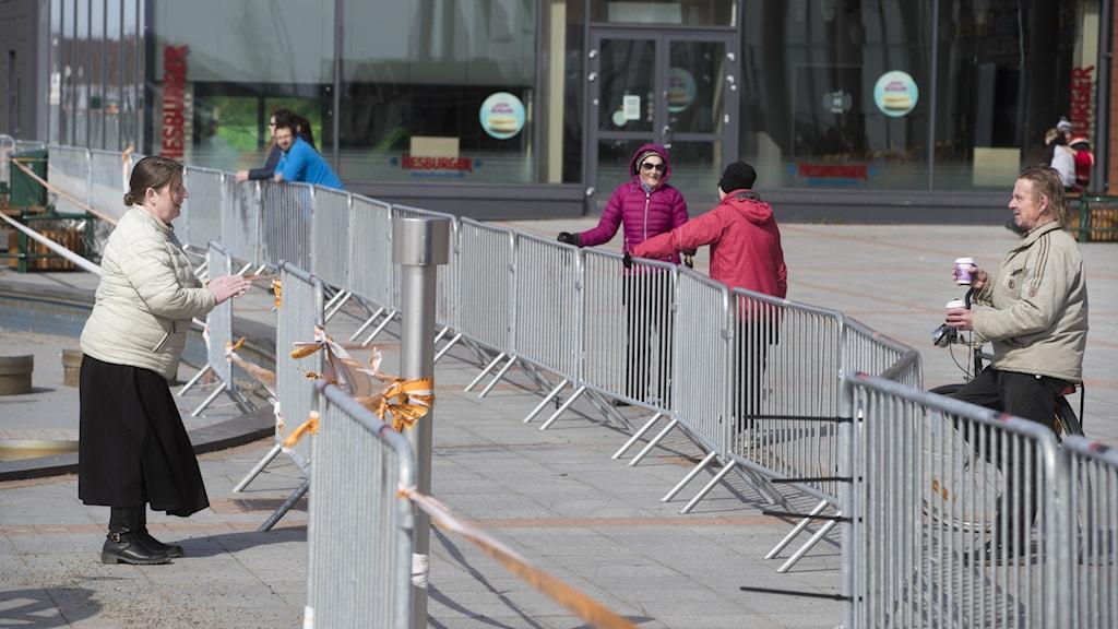 Gränsen mellan Finland och Sverige med ett stålstaket mellan. Kvinna står lutat mot gallret