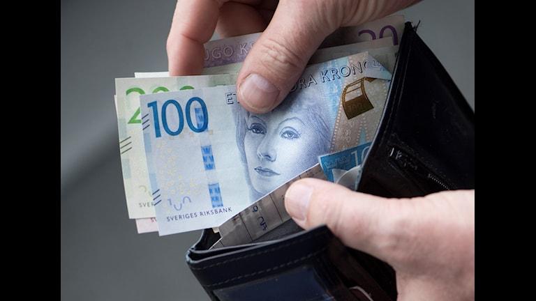 Svenska sedlar tas upp ur en plånbok.