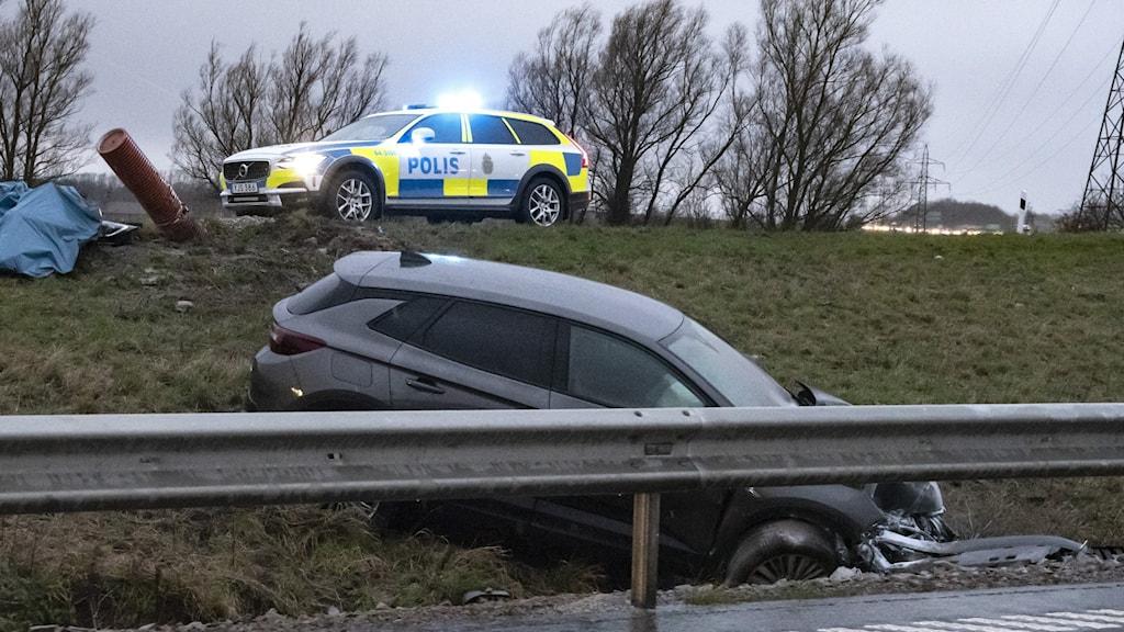 En bil har kört in i ett vägräcke, bakom står en polisbil med blåljus.