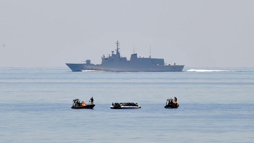 Fartyg i bakgrunden och några mindre gummibåtar framför det.