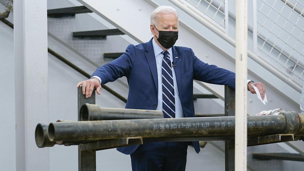 Kostymklädd man iförd svart munskydd står på podie