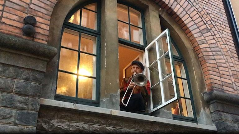 Man med keps spelar trombon ut genom ett fönster.