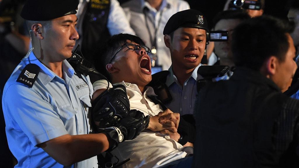 Demokratiaktivisten Joshua Wong grips.