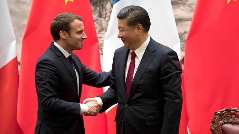 Frankrikes president Emmanuel Macron och Kinas Xi Jinping skakar hand under ett möte i Beijing.