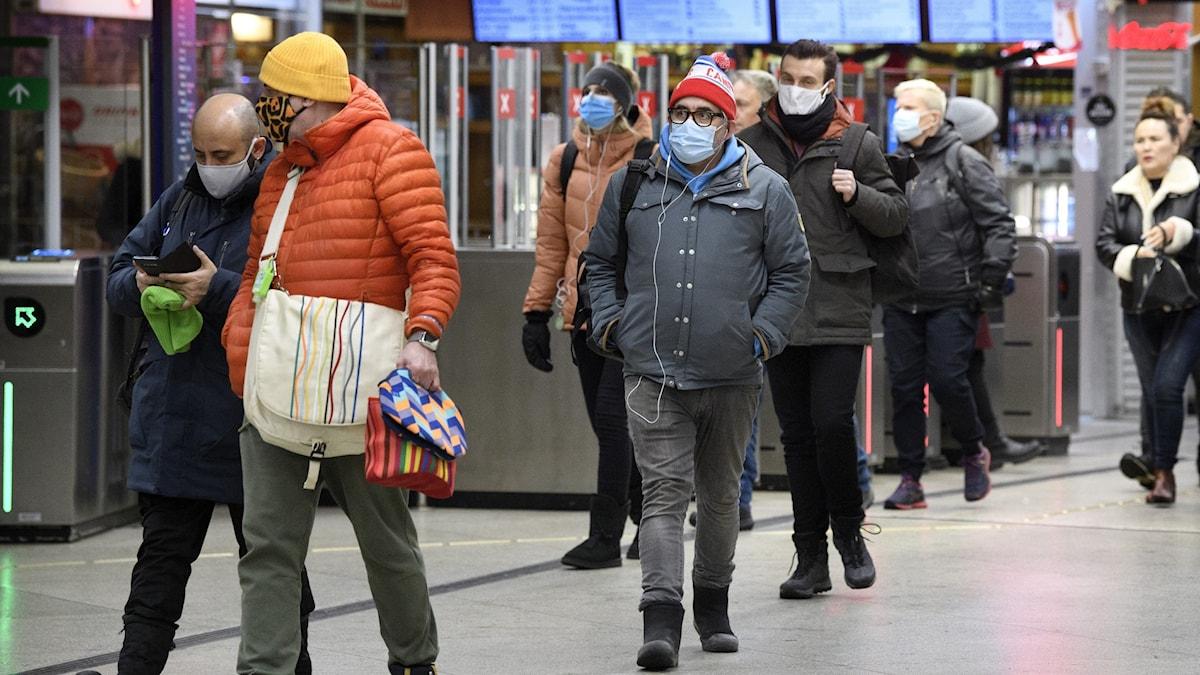 Flera personer med munskydd utanför tunnelbanespärrar.