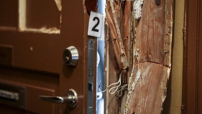 Bilden visar en upbruten dörr efter ett lägenhetsinbrott. Det är brytmärken på dörrkarmen och man ser en liten skylt med siffran 2 som polisens tekniker satt dit. Foto: Helena Landstedt/TT.