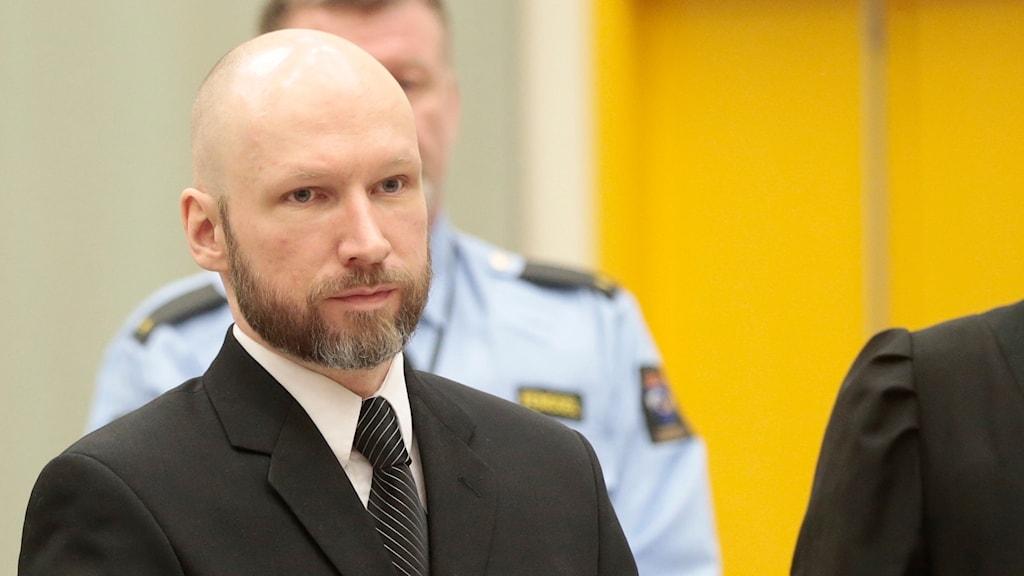 Anders Behring Breivik står och tänker, har kavaj och slips på sig