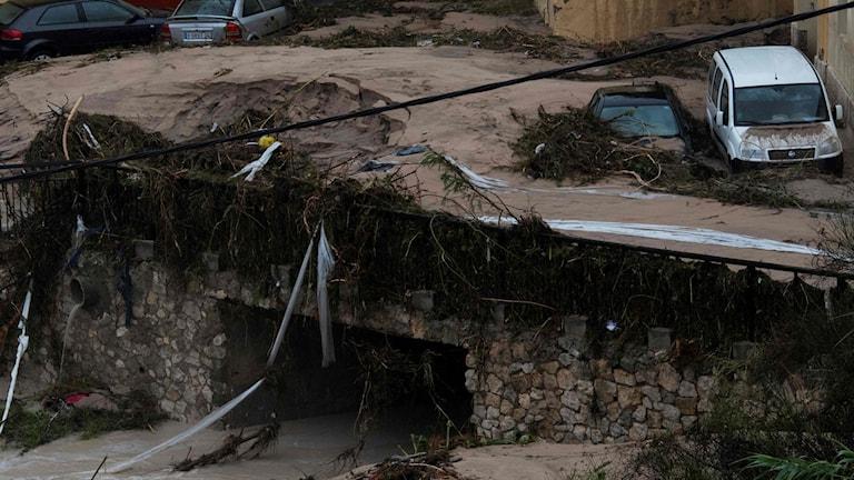 Förstörda bilar efter att en gata översvämmats i skyfall i Otinyent, i södra Spanien.