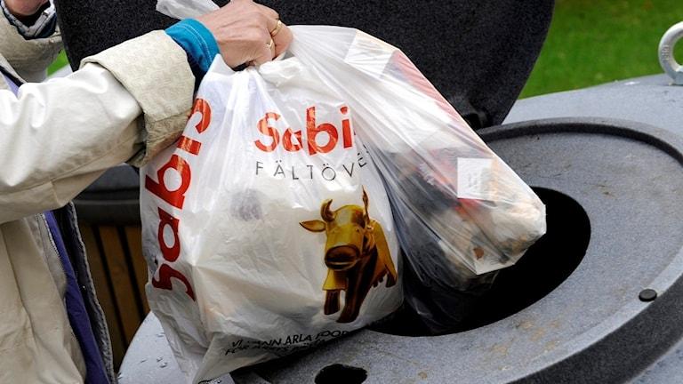 kvinna sorterar sopor