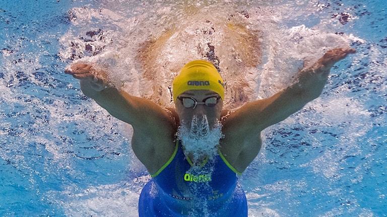 En kvinna simmar fjäril.