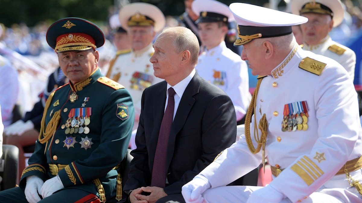 Putin sitter jämte en av den ryska flottans amiraler och överbefälhavaren under Marinens dag.